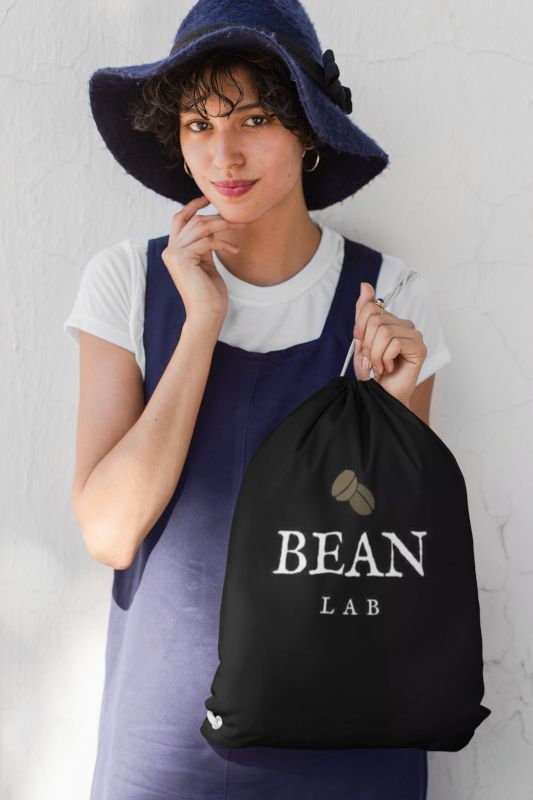 mockup-of-a-woman-with-a-floppy-hat-and-an-overall-holding-a-drawstring-bag-27584